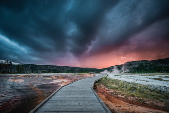 View of stormy clouds over boardwalk in Biscuit Basin during sunset