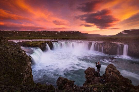 Man photographing Godafoss Waterfall during sunset