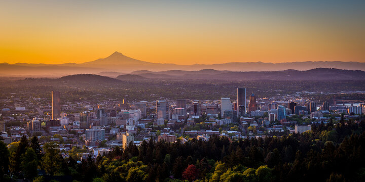 Scenic view of cityscape with Mount Hood in background during sunrise