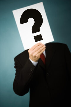 Businessman holding a sign with a question mark in front of face.