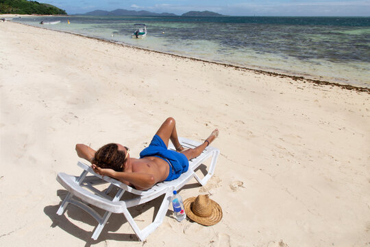 Male with curly hair, wearing blue swimsuits, tanning on sandy beach