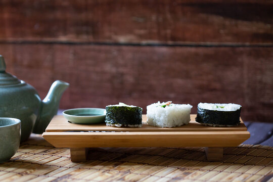 Three pieces of sushi lined up on wooden stand on bamboo mat.