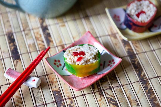 Close up shot of candy sushi and chopsticks on bamboo mat.