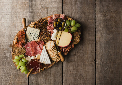 Top view of charcuterie board of meat, cheese, crackers on wood table.