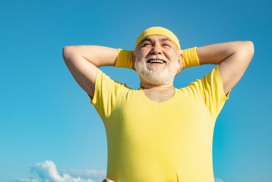 Freedom retirement concept. Elderly man practicing sports on blue sky background. Healthy and sport. Healthcare cheerful lifestyle.