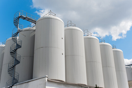 Rows of brewing tanks against the sky. Industrial beer production