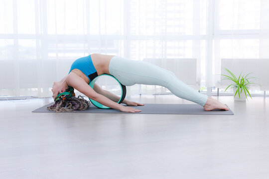 woman with dreadlocks in asana with yoga ring. Wheel ring for yoga helps relieve pain in spine