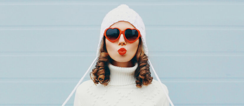 Winter portrait close up of young woman blowing red lips sending sweet air kiss wearing a white hat, sweater over blue background
