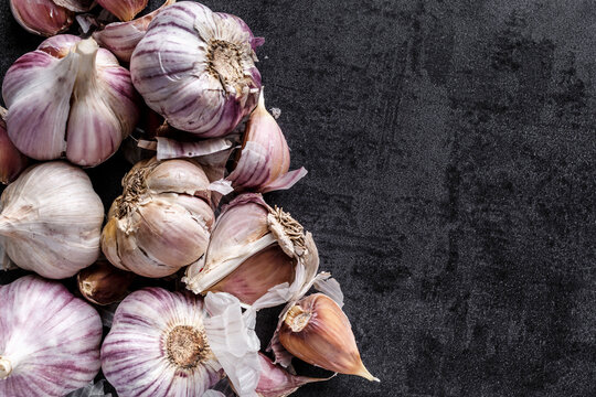natural food, heads of garlic on a black background. Top view. Copy space.