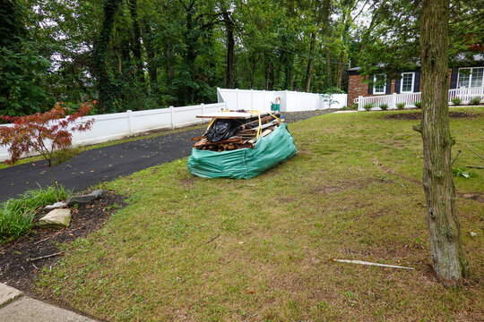 Large green bag full of wood and other construction debris on the lawn in front of a brick house by a asphalt driveway