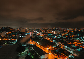 Cityscape view with orange city lights at night with a dark clouds background Fotomurales