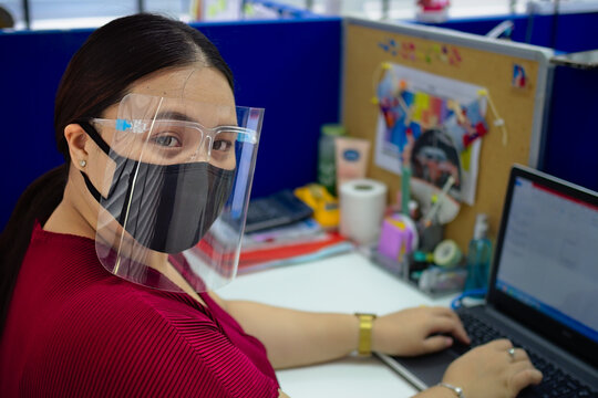 Closeup of a Southeast Asian female in a mask and face safety shield