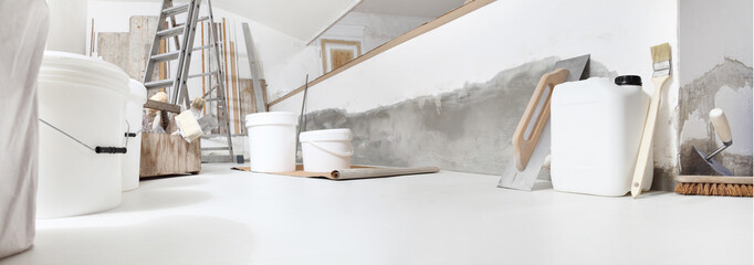 Low angle of indoor shot of construction or building site of home renovation with tools on white...
