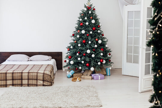 New Year's eve bedroom interior with red decor bed and Christmas tree with gifts