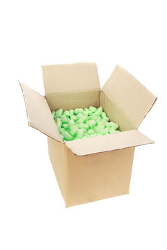Vertical shot of a cardboard box with green packing styrofoam peanuts