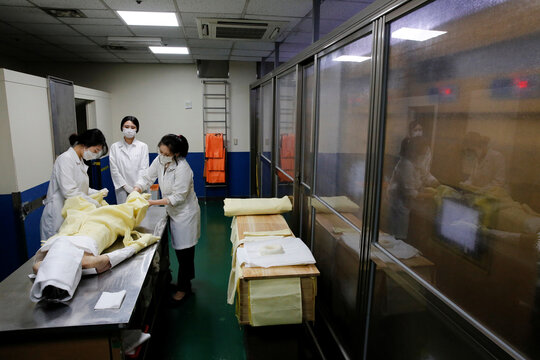Park Bo-ram, a funeral director, shrouds the body of a deceased at a funeral home in a medical center in Seoul