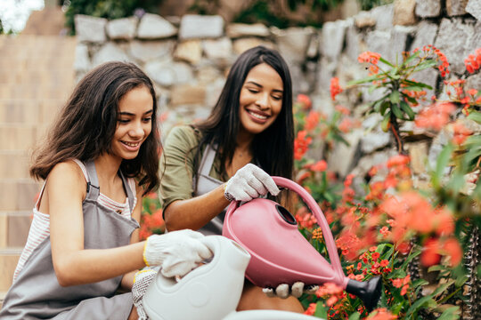 Latin mother and daughter taking care of plants at home