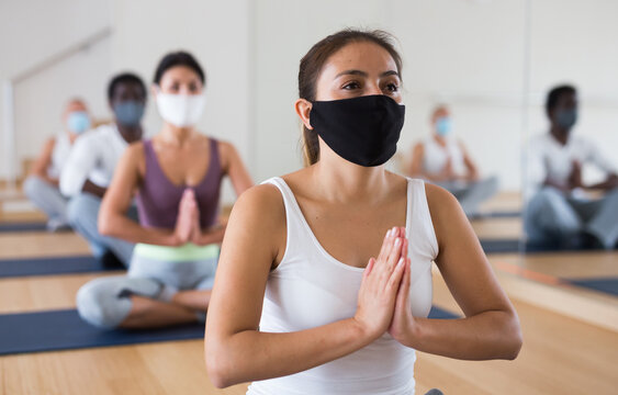 Young woman in face mask for viral protection sitting in lotus position practicing meditation at group yoga class