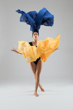 Graceful woman dancing with colorful cloth in studio