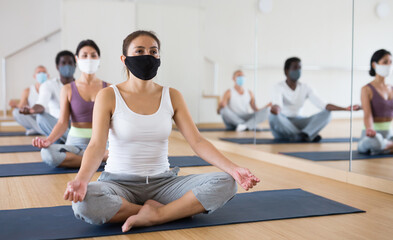 Man and woman in protective masks making yoga meditation in lotus pose in fitness center