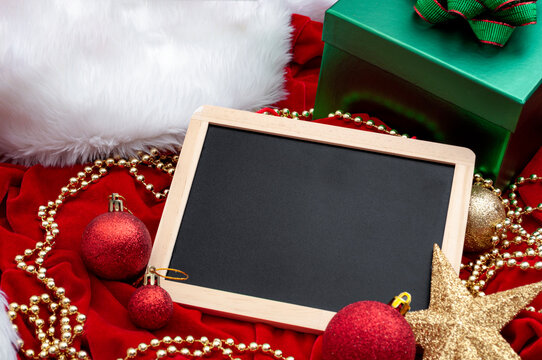 Merry Christmas and festive decoration concept with blackboard surrounded by vintage ornaments, gifts in green boxes and sparking baubles on red velvet background and copy space on the chalkboard