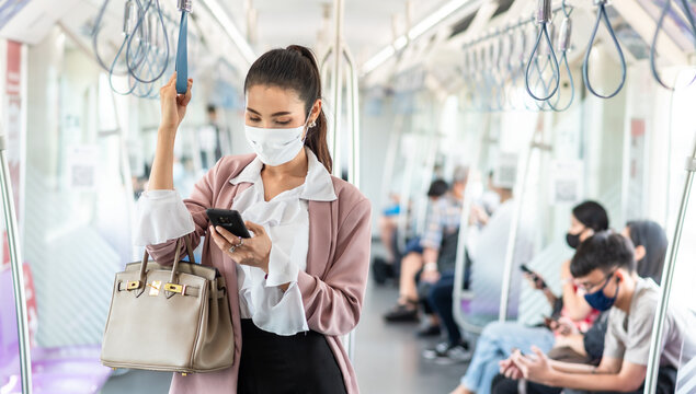 Asian business woman travelling on train in city wearing mask and pink blazer