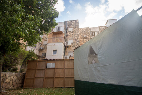 A beautiful sukkah made of wood inside the courtyard of a building, surrounded by trees and plants, Jerusalem, Israel.