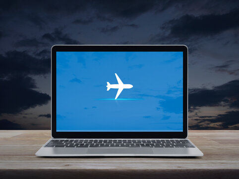 Airplane flat icon on modern laptop computer screen on wooden table over sunset sky, Business transportation online concept