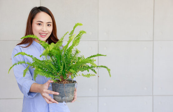 Young Asia woman happy smiling and holding green fern in plastics pot showing for sale.