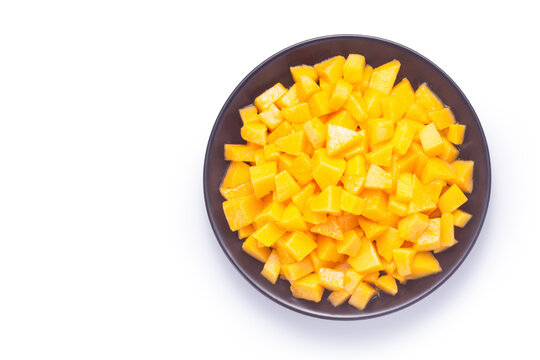 Diced mango in a black plate on white background. Top view.