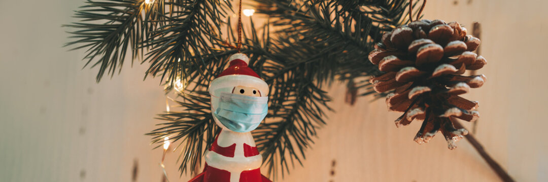 Christmas tree santa claus ornament wearing surgical face mask for coronavirus prevention during holiday family gathering. Banner of social distancing.