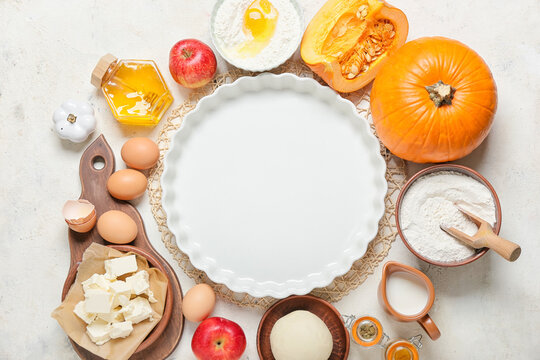 Ingredients for preparing pumpkin pie and baking dish on light background