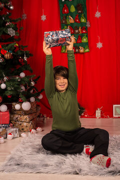 Happy kid holding  present over head
