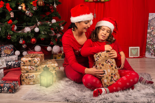 Cheerful mother and son opening Christmas gift
