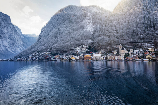 View over the lake of Hallstatt to the little village beneath the snow covered mountains on a cold winter morning, Austria