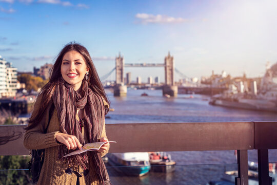 A beautiful female tourist in London holding a travel guide in front of the Tower Bridge on a sunny day, United Kingdom
