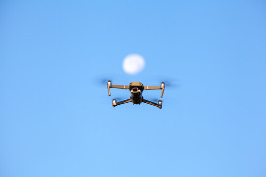 .A drone flying under the moon in blue sky
