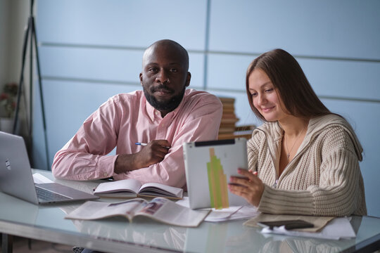 young African-American man with female colleague while working in cubicle at office. Ethnic entrepreneurs planning their work using laptop and cell phone. Staff relationship concept. selective focus