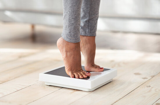 Cropped view of young black woman standing on scales at home, measuring her weight, closeup of feet