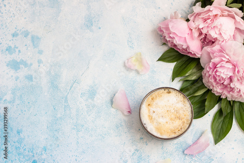 Morning cup of coffee or cappuccino and pink peonies on blue table. Top view. Creative breakfast for Woman or Mother day.