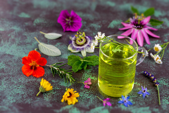 Herbal tea made from Fresh medicinal flowers and plants in transparent glass cup wooden background.