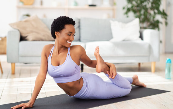Sporty African American woman stretching her leg on yoga mat at home