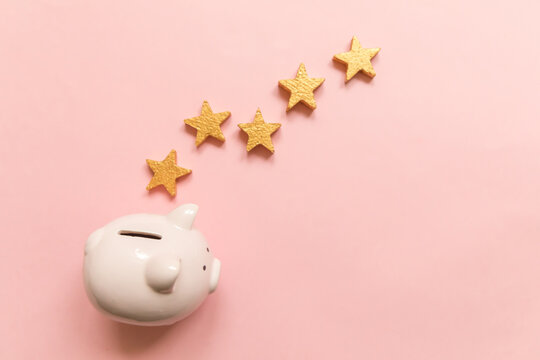 Simply minimal design piggy bank 5 gold stars isolated on pink background. Bank rating. Saving investment budget business retirement financial money banking concept. Flat lay top view copy space.