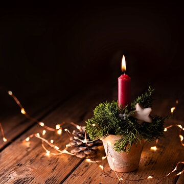 Christmas candle on rustic wood background in old clay pot, Advent decoration with magic lights and natural elements on dark square background with copy space - Xmas card