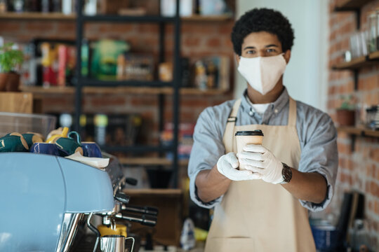 Waiter in medical protective mask serves coffee in restaurant during coronavirus pandemic and new normal