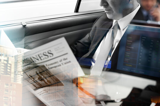 Businessman reading newspaper in car with city background overlay