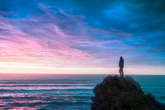 A man standing at lonely rock  against a beautiful sunrise, clouds reflection in water