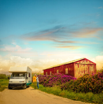 Happy  couple standing in front of camping car, on Portugal road