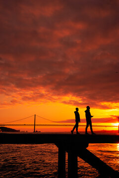 Silhouette of lovers walking with a  bridge in the background sunset time Lisbon