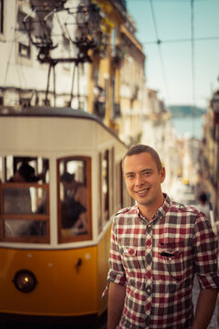 Young smiling man tourist standing near the  retro yellow tram on the street in Lisbon city, Portugal